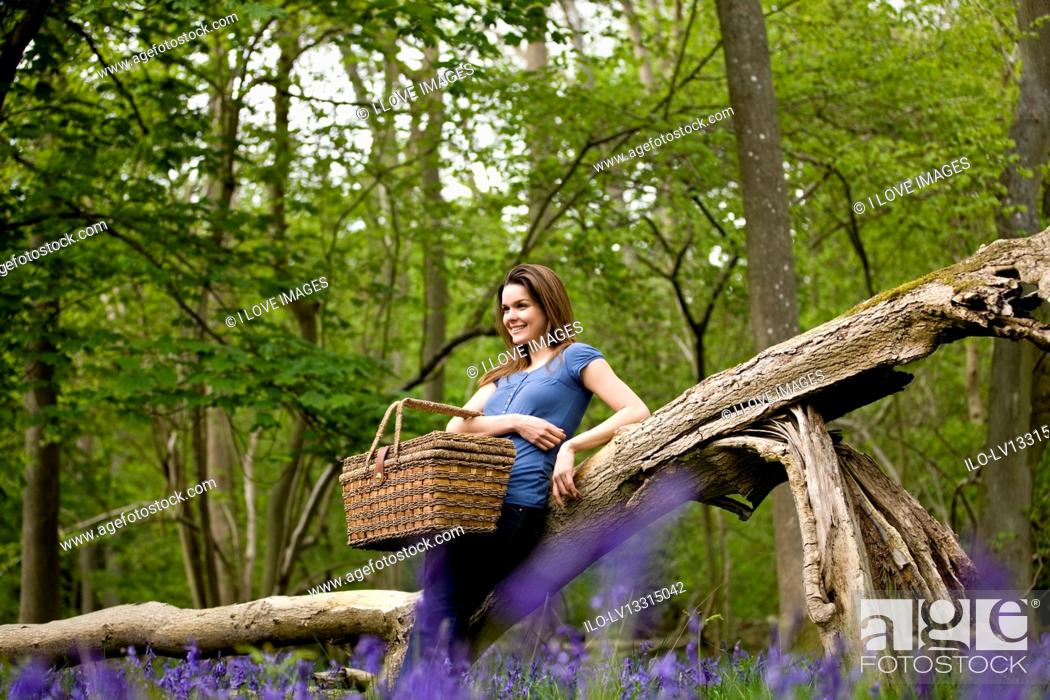 Stock Photo: A young woman leaning against a tree, holding a picnic basket.