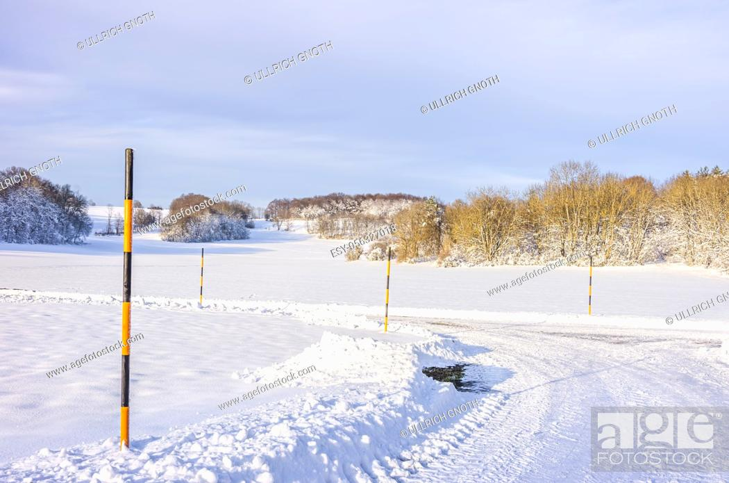Stock Photo: Snow poles at the edge of a country lane in a winter scenery.