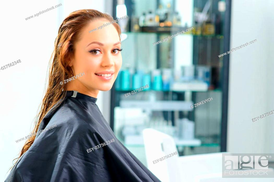 Stock Photo: In the salon. Young attractive woman is smiling lightly while sitting in the salon with her hair clean and wet.