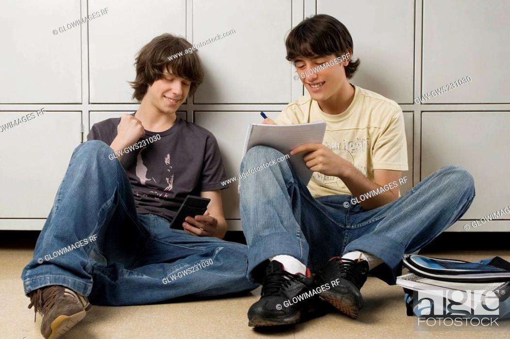Stock Photo: Young man sitting with a teenage boy and writing on a notebook.