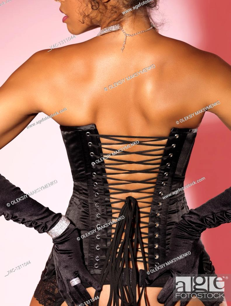 Stock Photo: Beautiful woman wearing a black corset and gloves.
