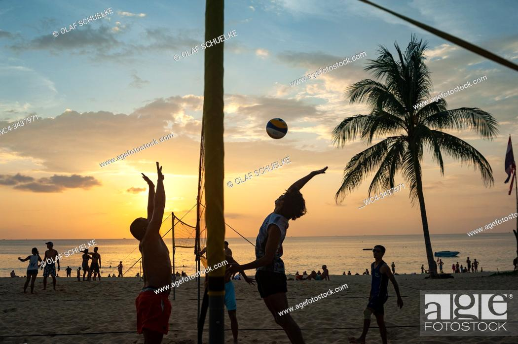 Stock Photo: Phuket, Thailand, Asia - A group of locals plays volleyball in the sunset on Karon Beach.