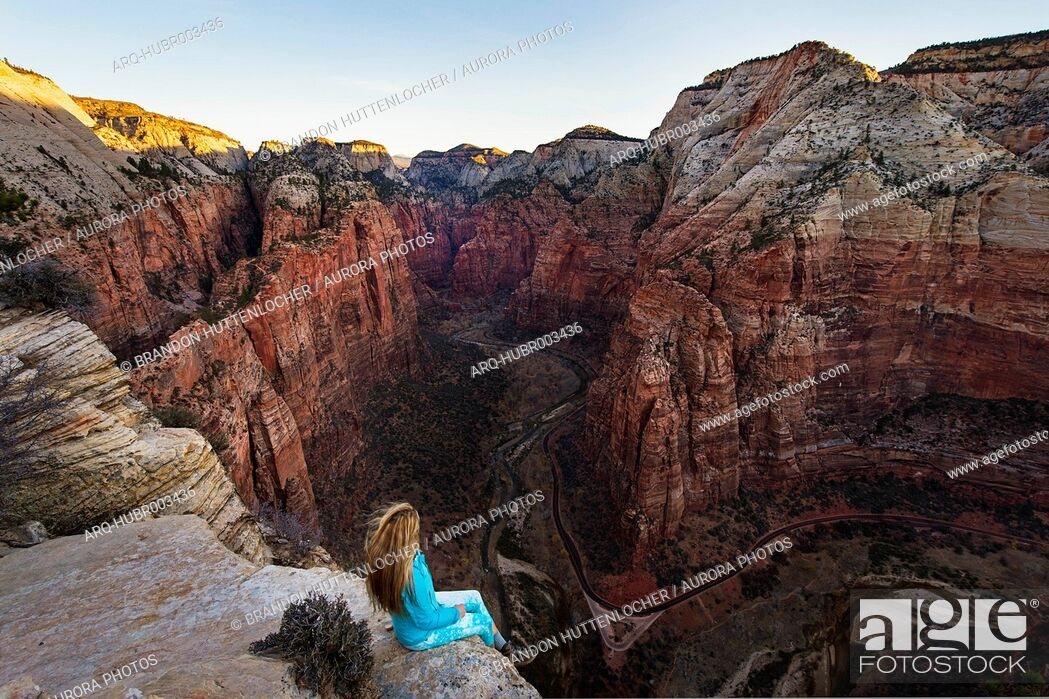 Imagen: Woman sitting on edge of cliff and looking at view of canyon from Angels Landing, Zion National Park, Utah, USA.