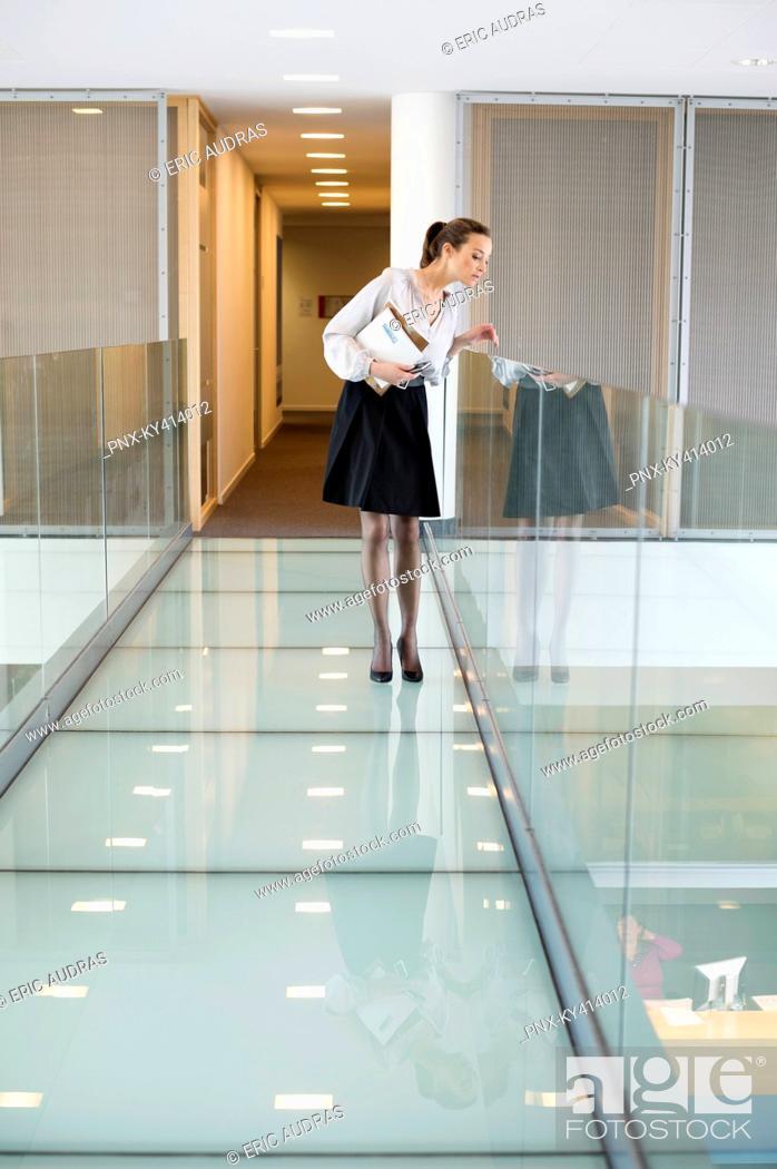 Stock Photo: Businesswoman peeking through glass in a corridor.