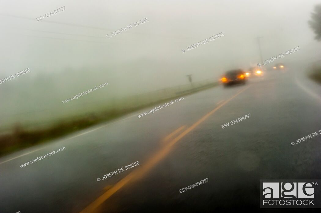 Stock Photo: A wet 2 lane paved country road fading to the horizon with on-coming traffic during a rain storm in southern Alabama, USA.