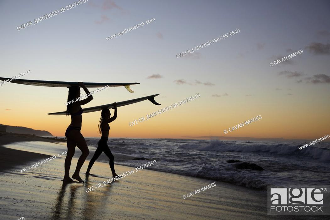 Stock Photo: Girls paddling out for Sunset Surf on the North Shore in Hawaii.