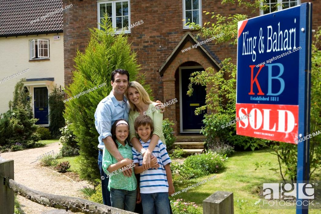 Stock Photo: Family of four in front of house with 'sold' sign, smiling, portrait.