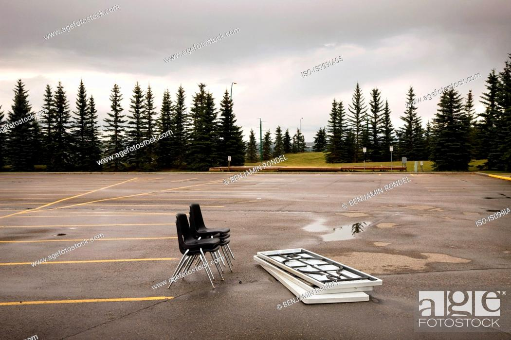 Stock Photo: Chairs and tables left in a parking lot.