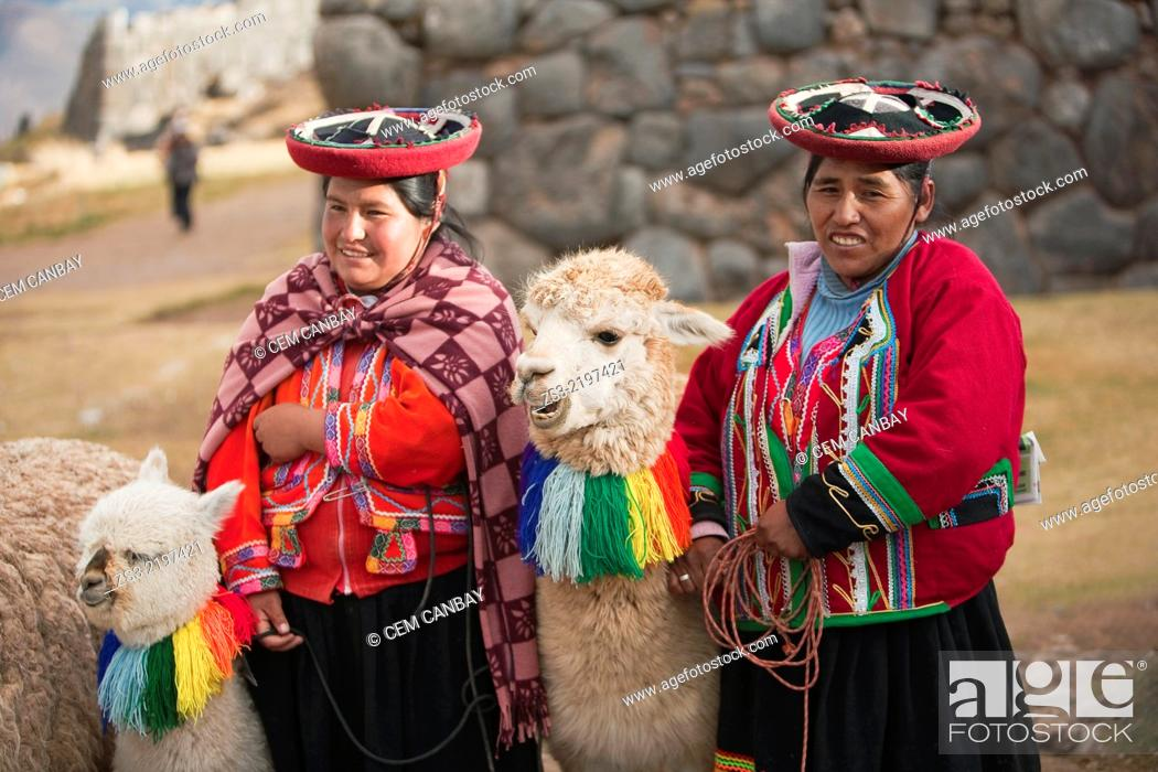 Quechua-Peruvian women with traditional costume and llamas