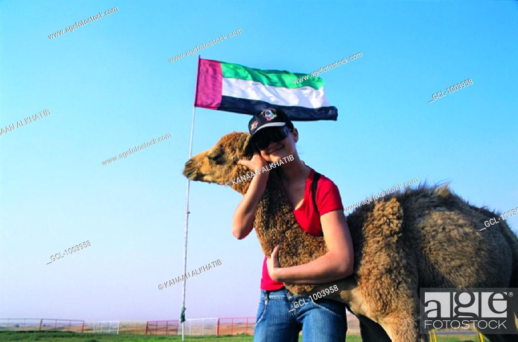 Stock Photo: Tourist hugging a camel, United Arab Emirates.