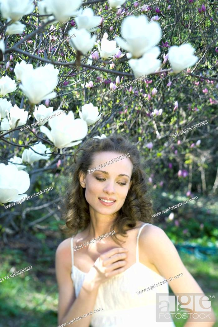 Stock Photo: Young woman standing under flowering tree, hand in hair, looking away.