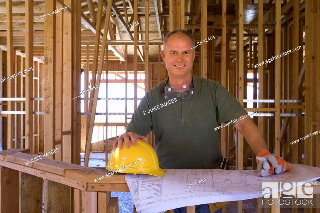 Stock Photo: Builder with blueprints in partially built house, smiling, portrait.