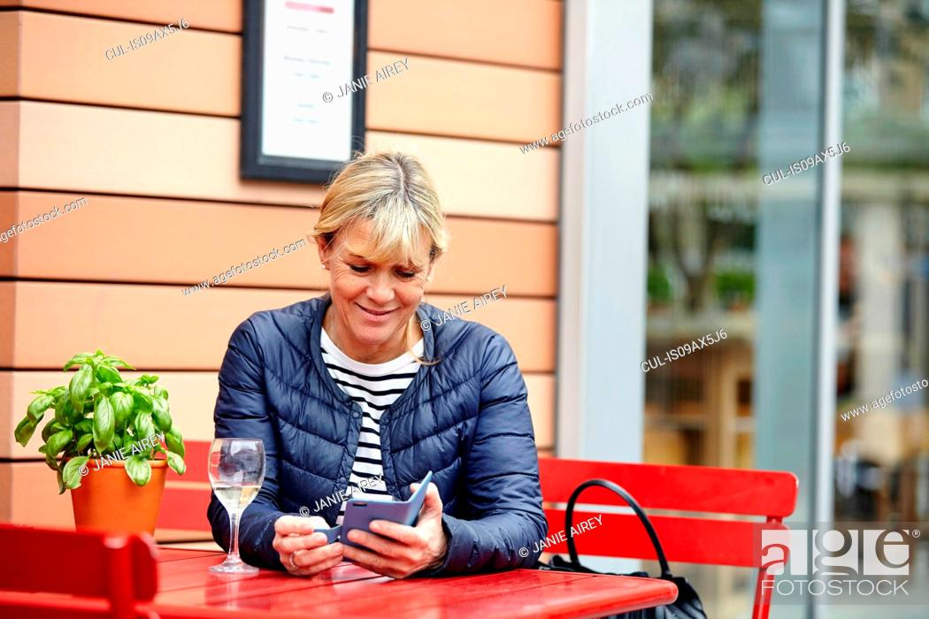 Stock Photo: Mature woman reading smartphone texts at sidewalk cafe.