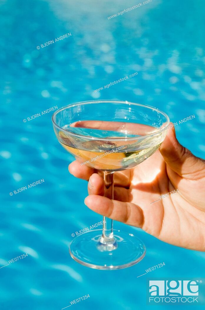 Stock Photo: Hand holding champagne glass in front of pool.