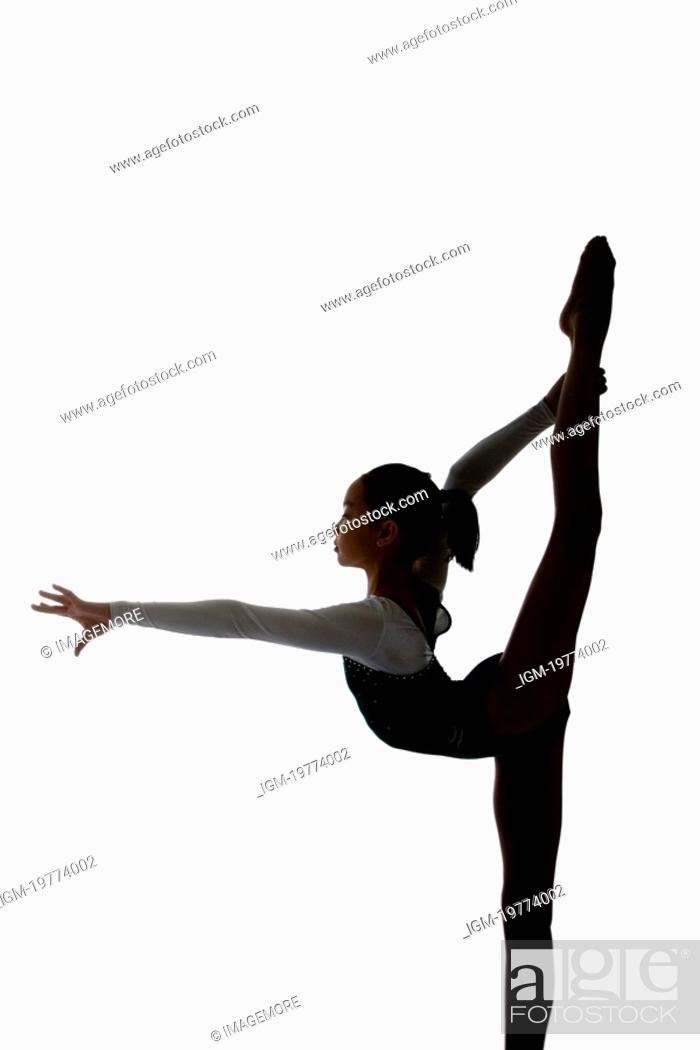 Stock Photo: Girl practicing gymnastic pose on pad, silhouette.