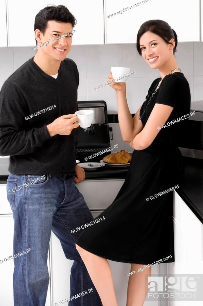 Stock Photo: Portrait of a young couple holding their coffee cups in the kitchen and smiling.