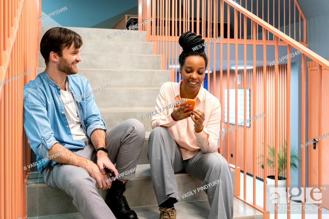 Stock Photo: Smiling male professional looking at female colleague while her using smart phone in office.