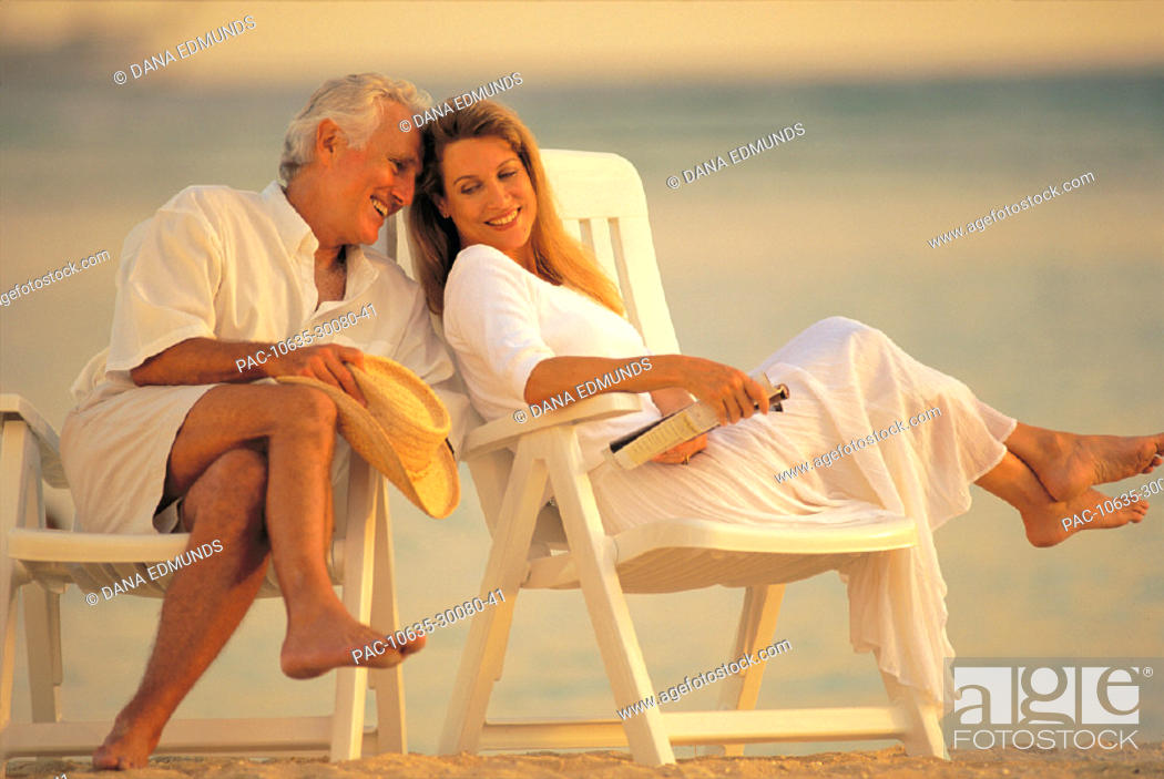 Imagen: Senior man at the beach in chairs laughing with woman, couple relaxing.