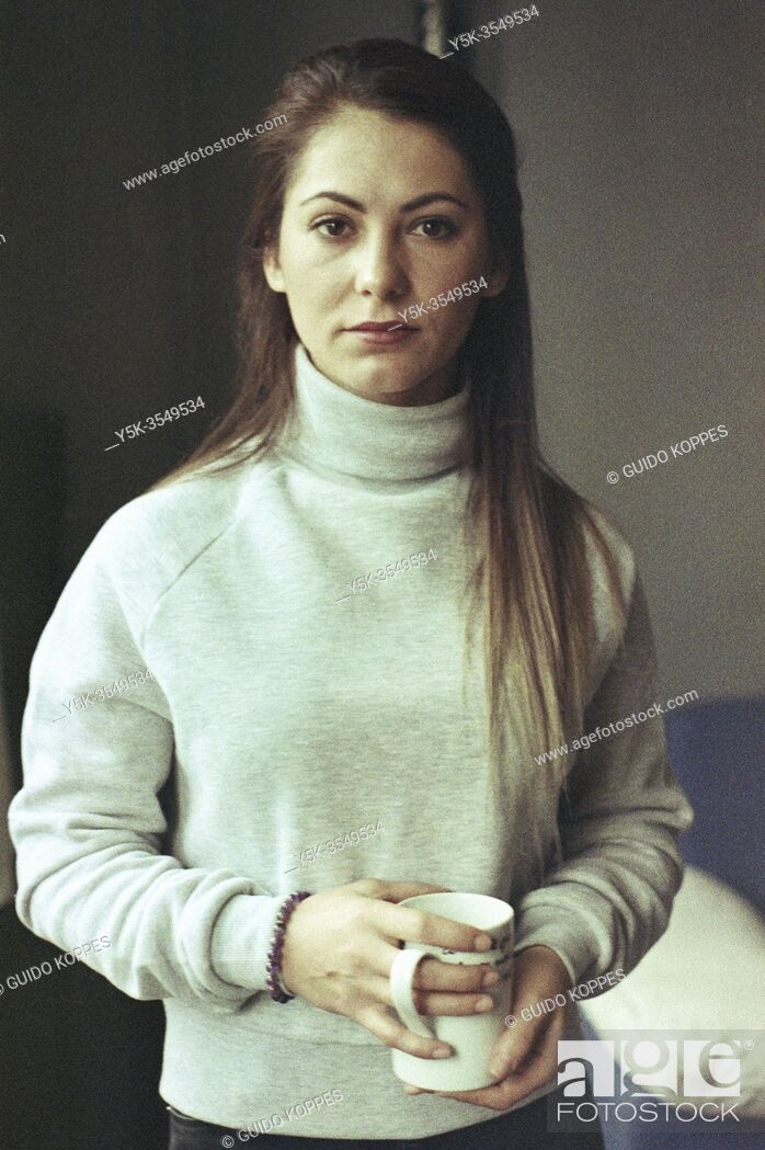 Stock Photo: Tilburg, Netherlands. Portrait young adult, brunette woman holding her cup of coffee. Shot on Analog Color Film in 2020.