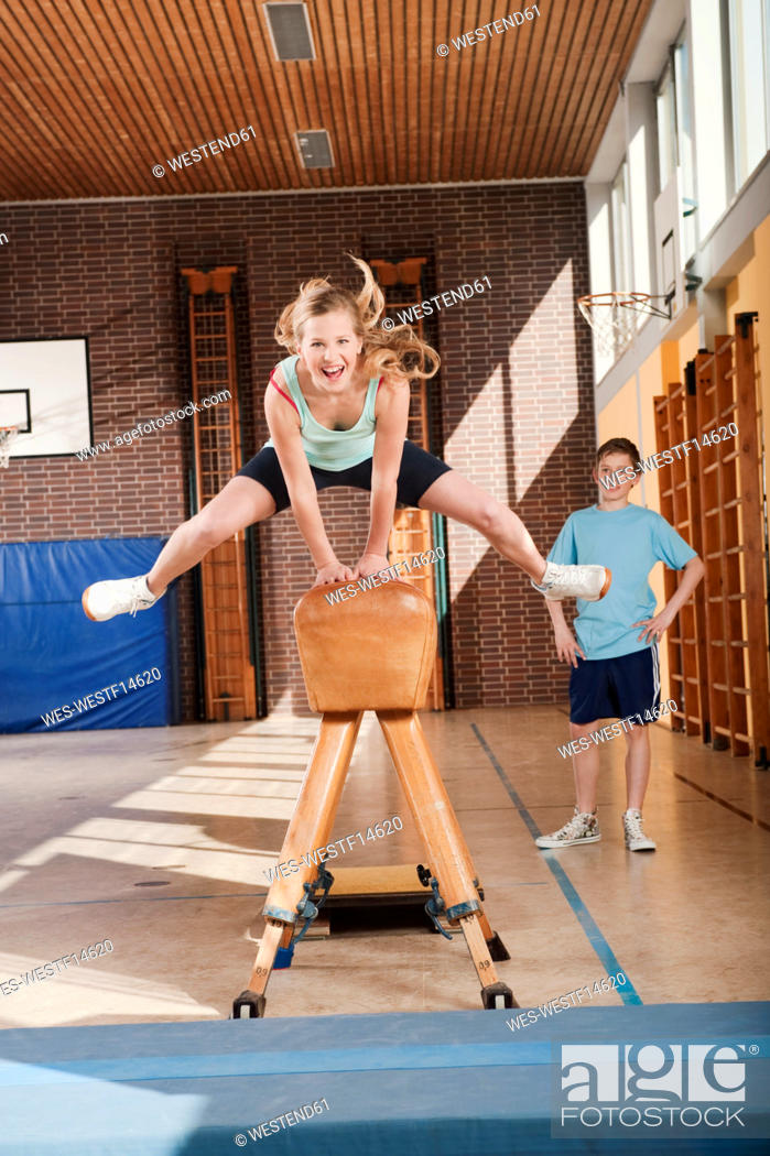 Stock Photo: Germany, Emmering, Girl 12-13 jumping with boy standing in background.