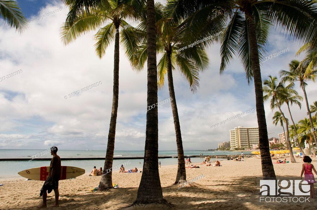 Stock Photo: Surfer on the famous Waikiki Beach. Kalakaua Avenue. O'ahu. Hawaii. Located on the south shore of Honolulu, the world-famous neighborhood of Waikiki was once a.