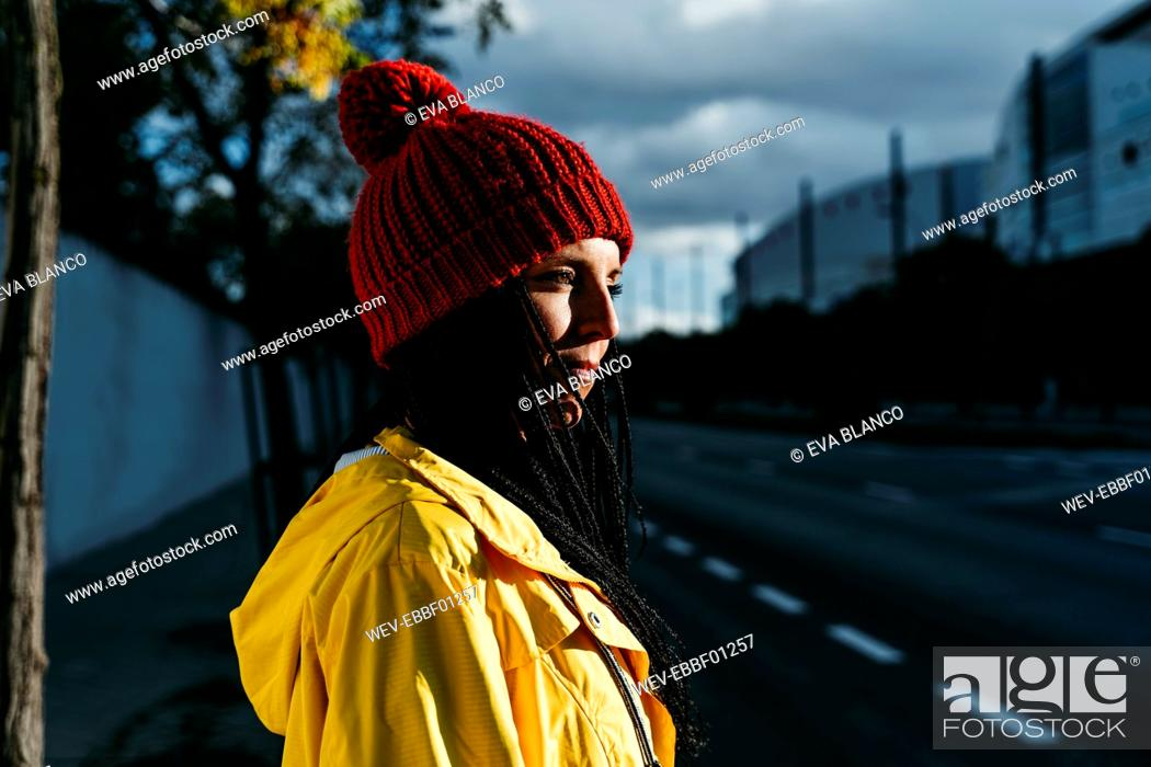 Stock Photo: Thoughtful woman wearing knit hat standing on street during sunset.