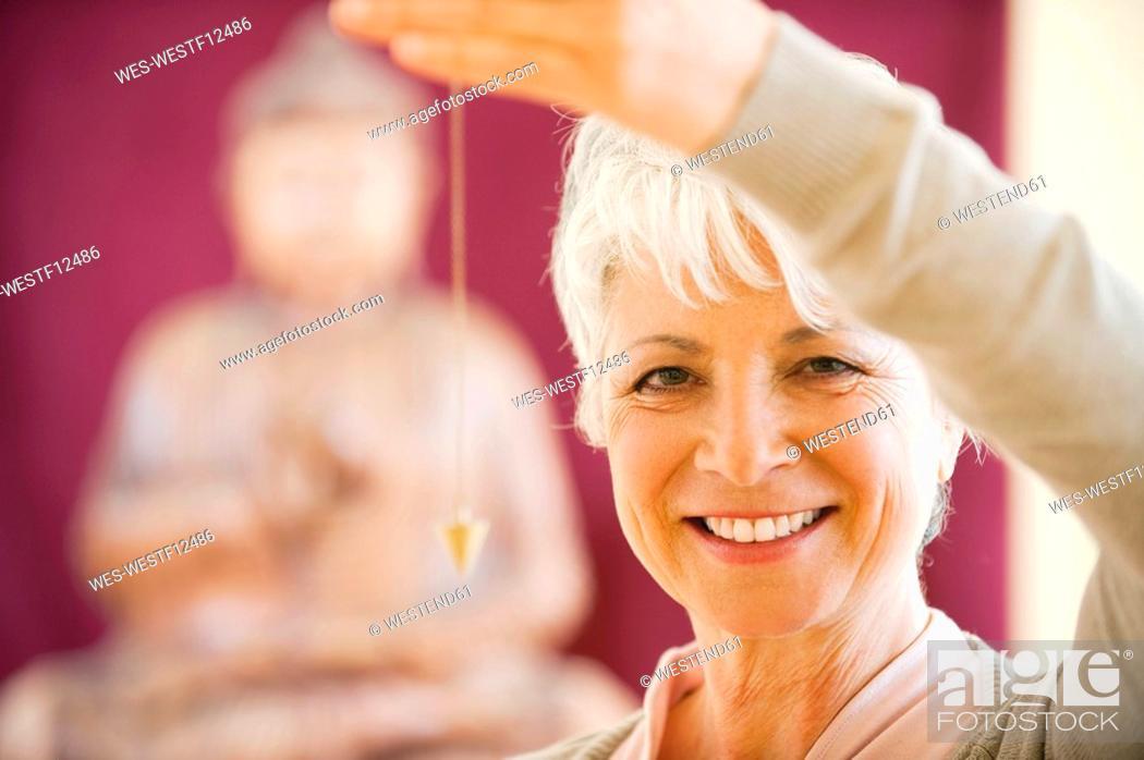 Stock Photo: Senior woman holding pendulum, smiling, portrait.