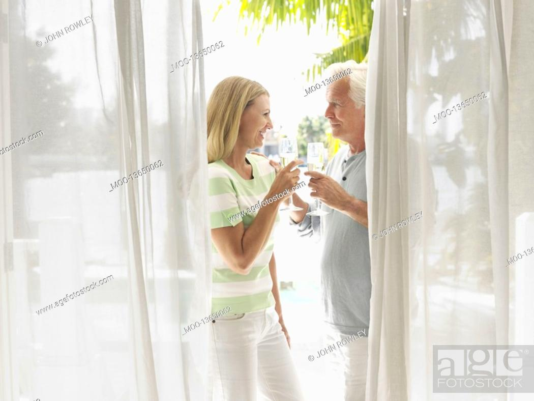 Stock Photo: Couple toasting with champagne flutes standing on verandah side view.