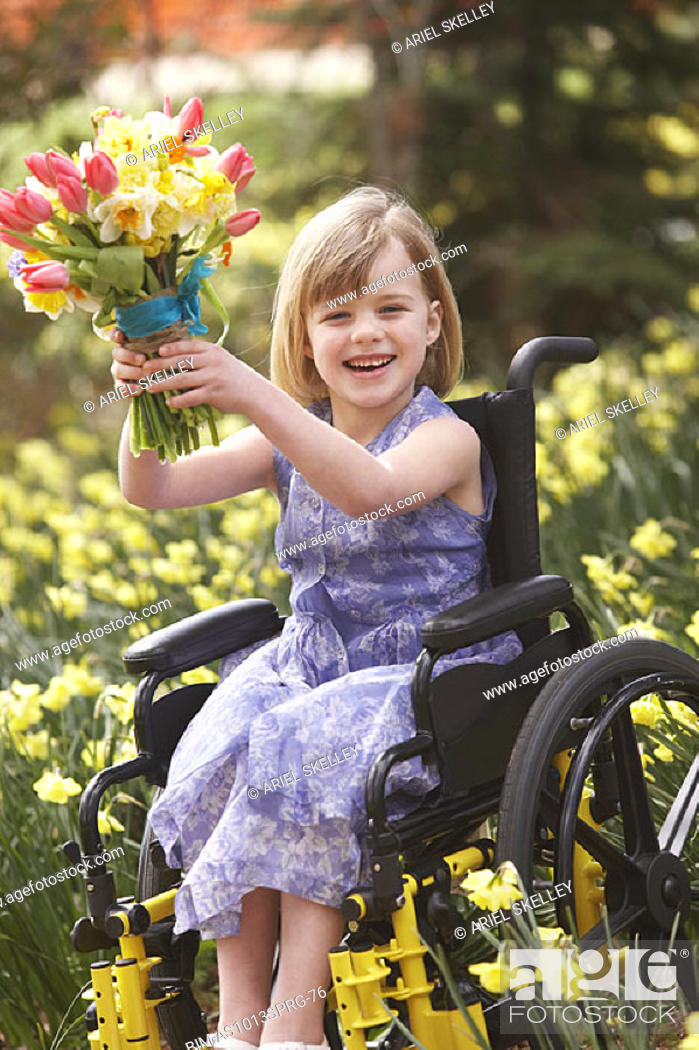 Stock Photo: Girl in wheelchair with bouquet of flowers outdoors.