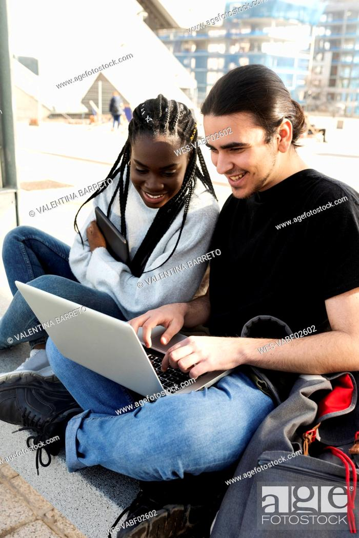 Stock Photo: Happy young couple using laptop at tram stop.