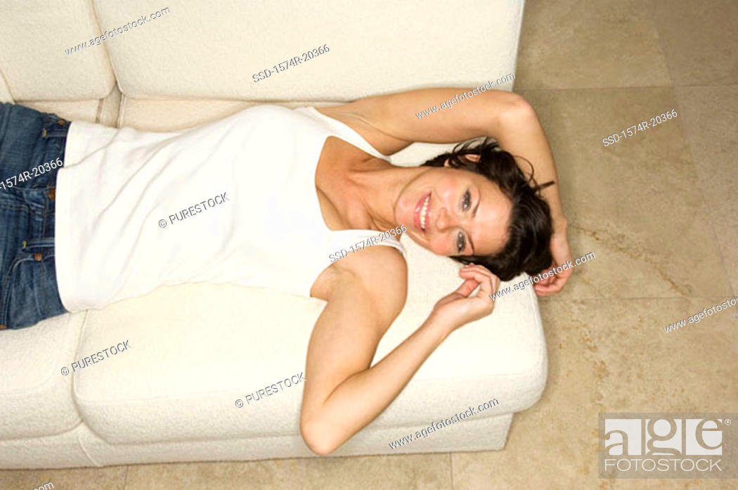 Stock Photo: High angle view of a young woman lying on a couch and smiling.