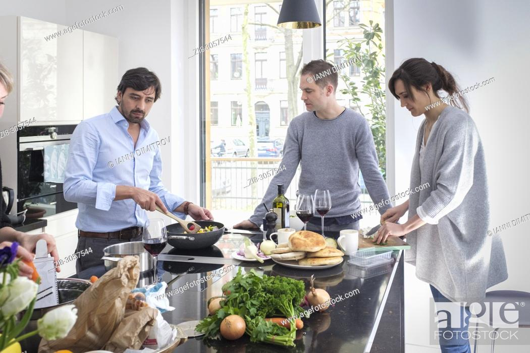 Stock Photo: Group of friends preparing vegetarian food together while laughing and enjoying themselves in the kitchen.