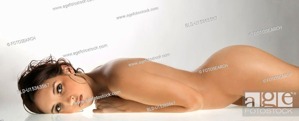 Stock Photo: Nude Caucasian young adult woman lying on stomach looking at viewer.