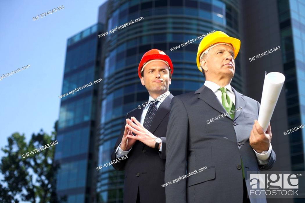 Stock Photo: Two businessman wearing hardhats.