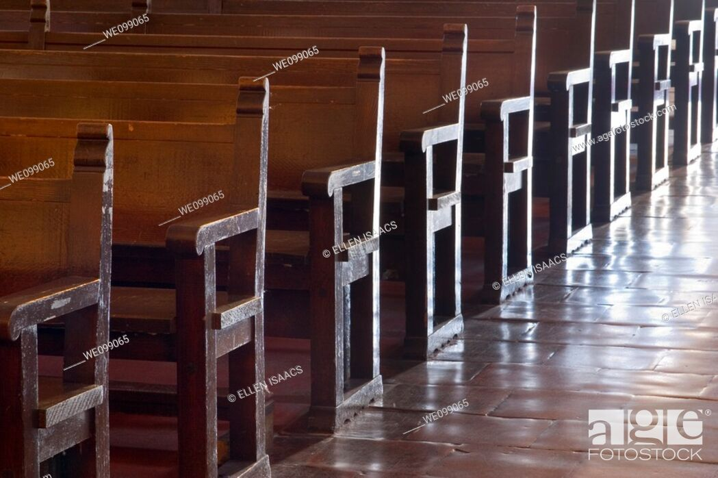 Stock Photo: Rows of wood pews for worship in the Carmel Mission Basilica church Mission San Carlos Borromeo del Rio Carmelo in Carmel, California.