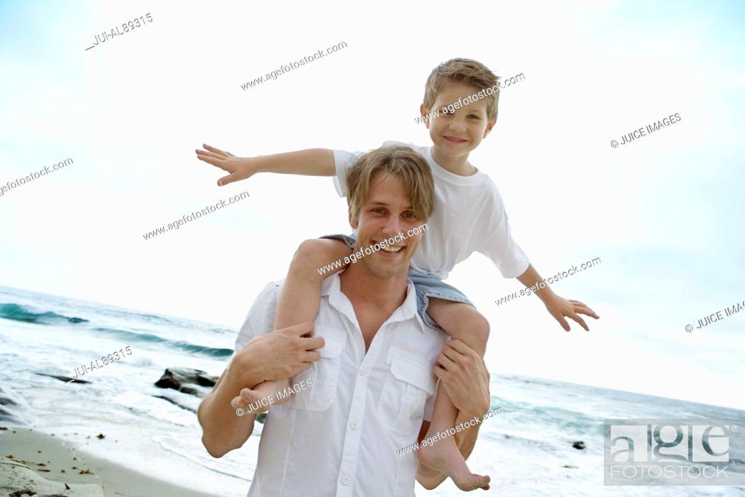 Imagen: Father carrying son on shoulders at beach.