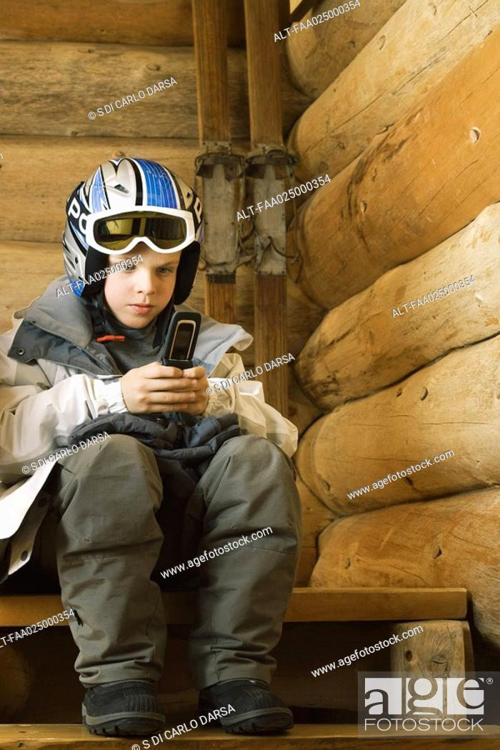 Stock Photo: Boy in ski gear sitting, using cell phone.