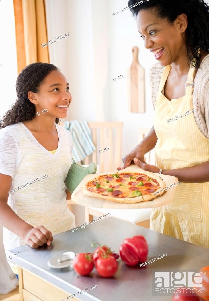 Stock Photo: Mother and daughter preparing pizza for dinner.