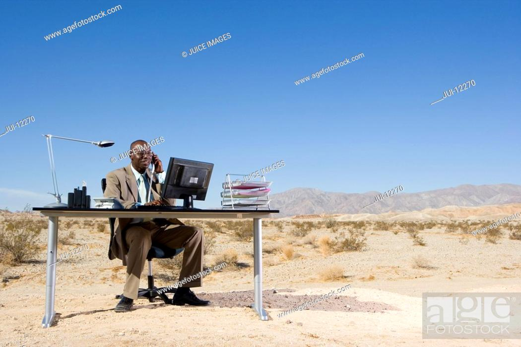 Stock Photo: Businessman at desk in desert, using telephone and computer, low angle view.