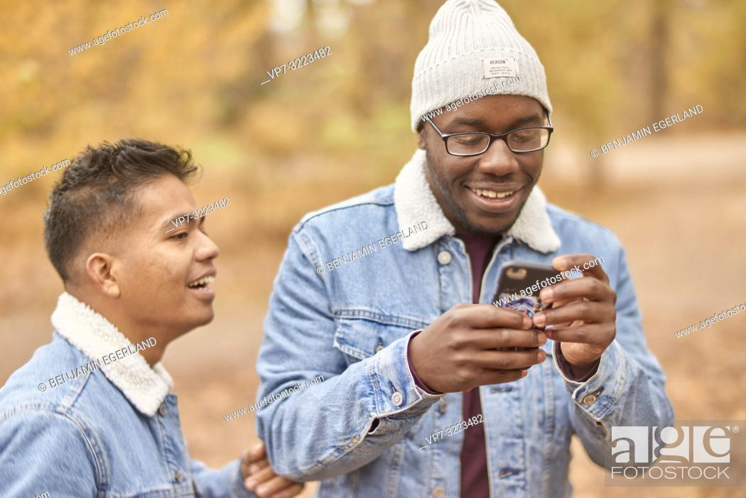 Stock Photo: friends looking at smartphone, in park, nature, in Munich, Germany.
