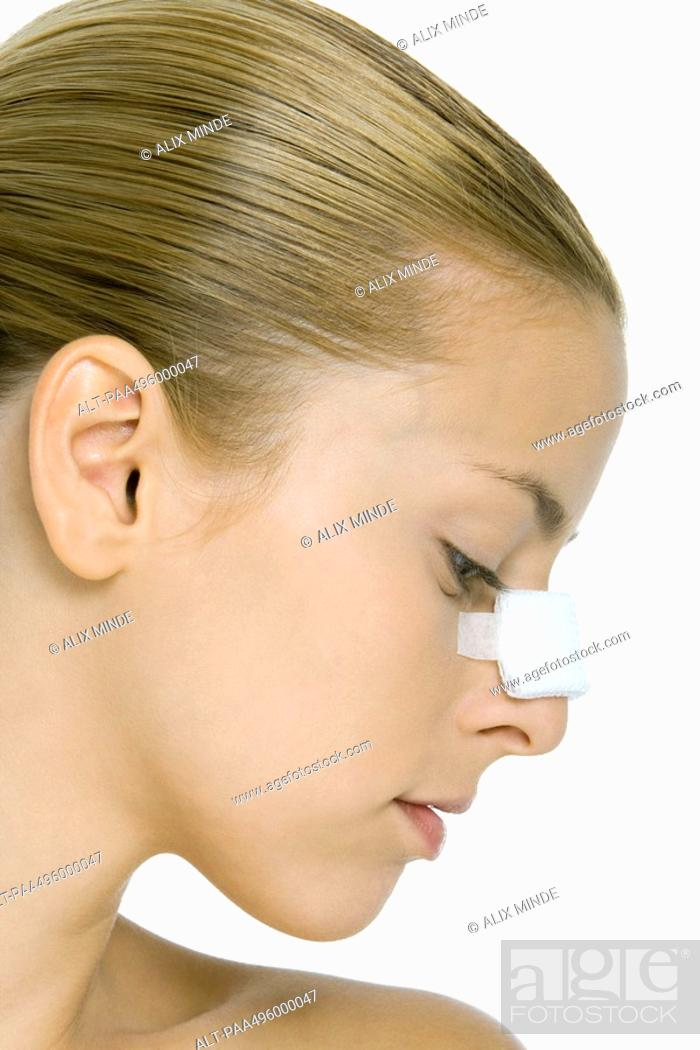 Stock Photo: Young woman with bandaged nose, profile.