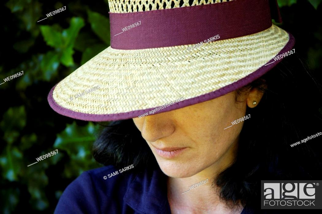 Stock Photo: Portrait of a woman wearing a straw hat and looking sad.