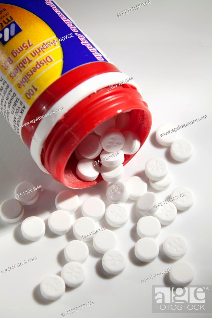 Stock Photo: low dose 75g aspirin pills around open container.