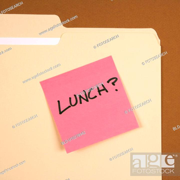 Stock Photo: Folder with pink sticky note reading lunch on a brown background.