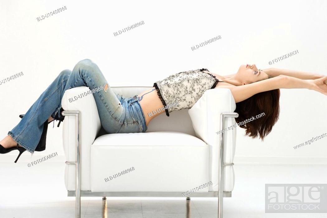 Stock Photo: Portrait of woman laying back over an armchair.