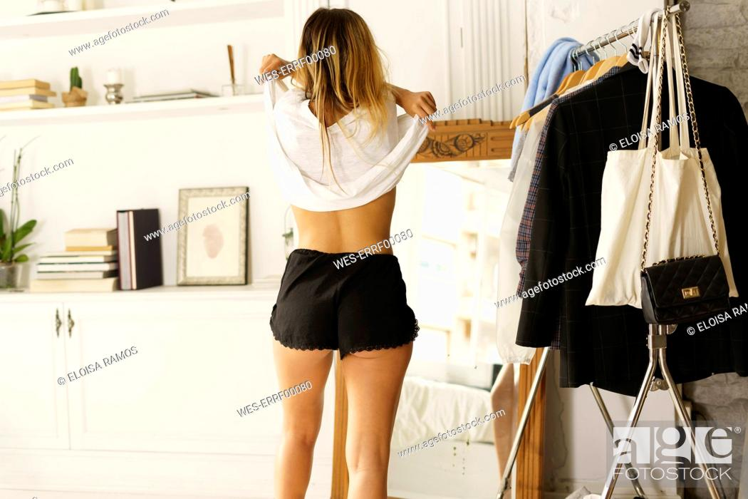 Stock Photo: Rear view of young woman undressing at home.