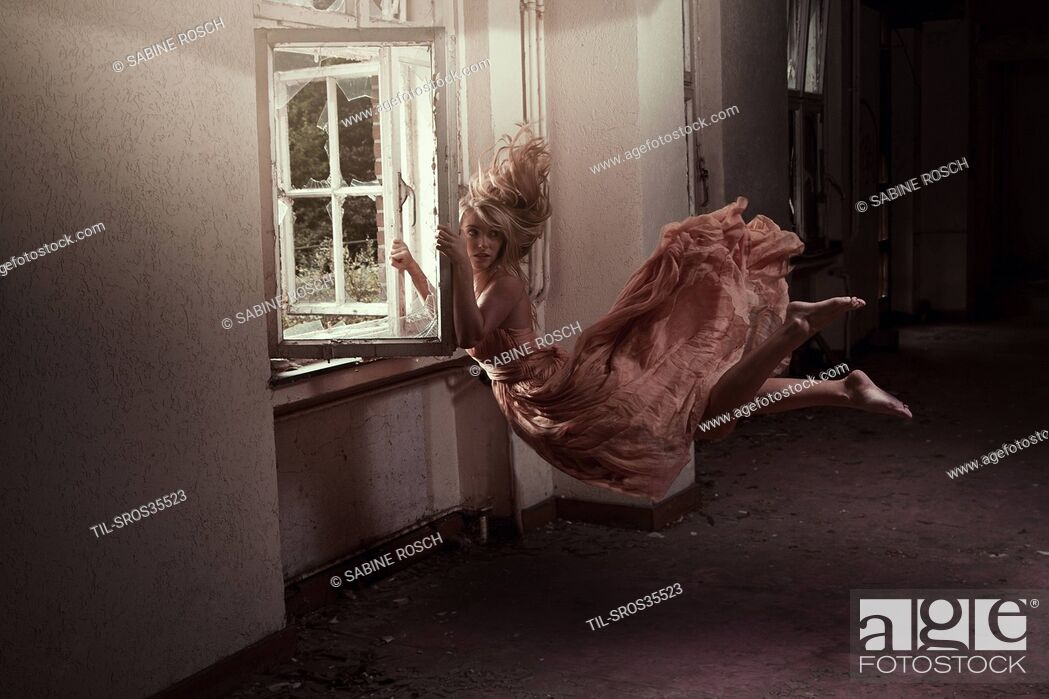 Stock Photo: Conceptual image of female floating at an old window.
