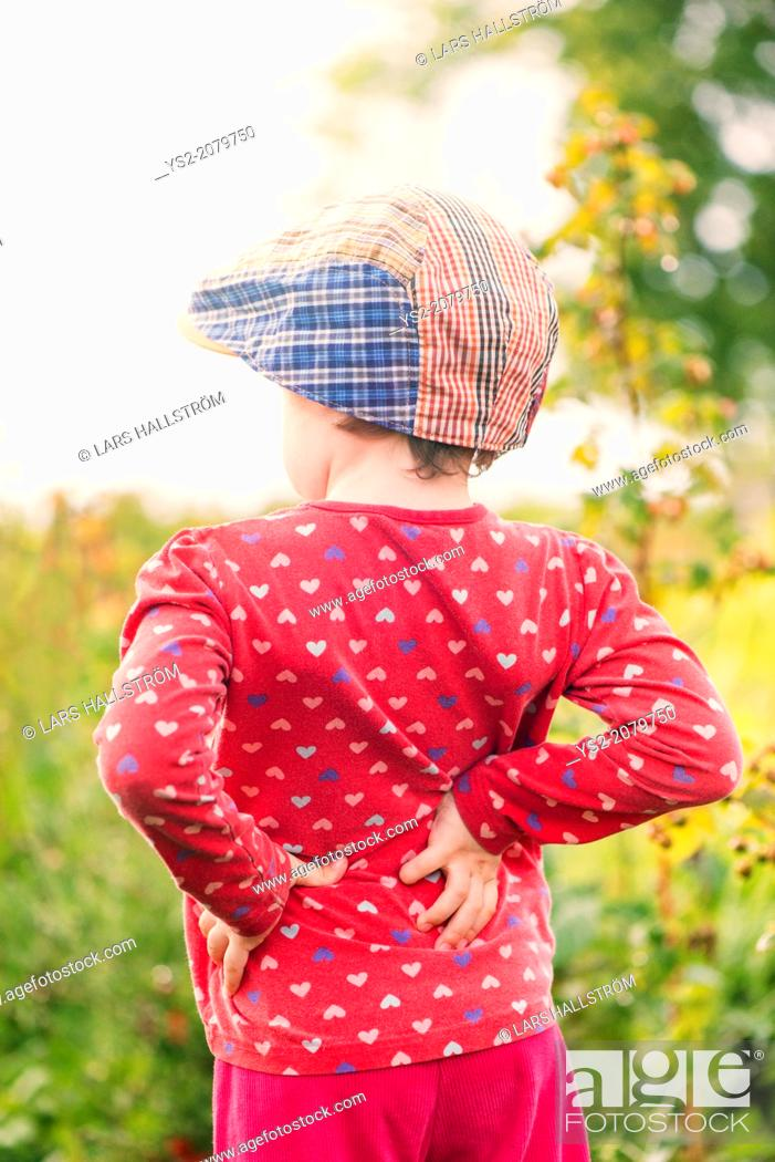 Stock Photo: Back view of young child standing in garden watching green plants and flowers.