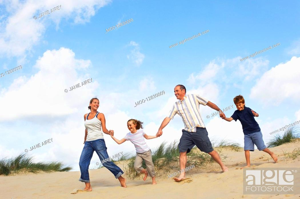 Stock Photo: Family holding hands and running down sand dune on beach.