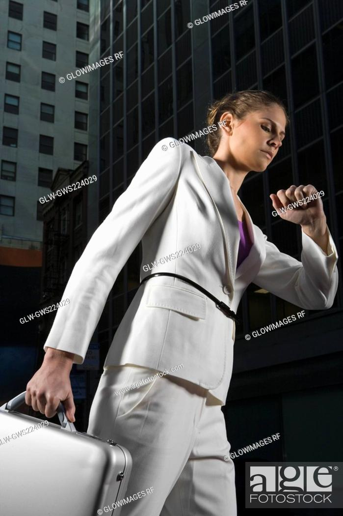Stock Photo: Low angle view of a businesswoman walking and checking the time.